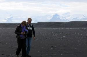 Marit en Reidar struinen over het strand op zoek naar zand en mooie stenen, met gletscher op de achtergrond