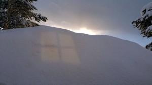 De zon weerspiegelt van raam op de sneeuwberg