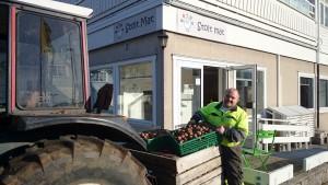Kristian komt met zijn trekker aardappels bij de winkel brengen
